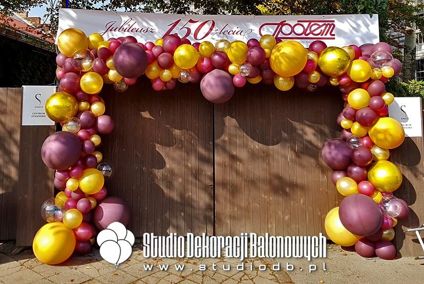 Organiczna brama z balonów jako dekoracja wejścia na wydarzenie firmowe.