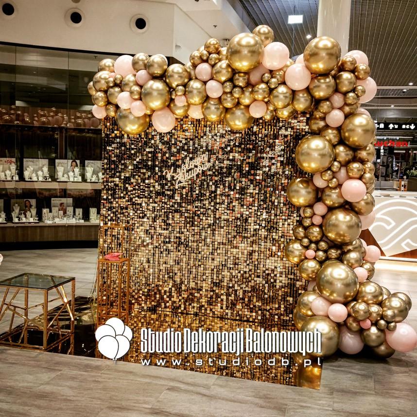 Złota ścianka cekinowa z girlandą balonową jako efektowne tło do zdjęć